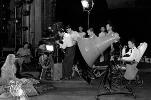 Orson Welles (seated by the giant megaphone) directs a scene from 1941′s 'Citizen Kane' while laid up with a broken ankle he suffered during the shoot. The visor-adorned gentleman next to the camera is cinematographer Gregg Toland. Production still photographer: Alexander Kahle © Warner Brothers