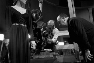 On the set of Notorious, Alfred Hitchcock sets up the shot in which the camera swoops down into the party to an extreme close-up of the key hidden in Ingrid Bergman's hand. Photo by the great photojournalist Robert Capa, who was romantically involved with Bergman at the time